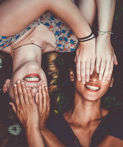 zwei Frauen liegend, halten sich gegenseitig die Augen zu, lachend
