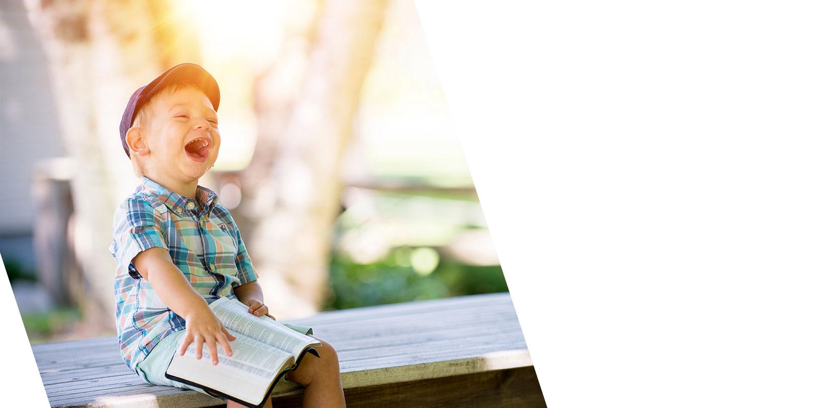 kleiner Junge mit Mütze und Buch lachend