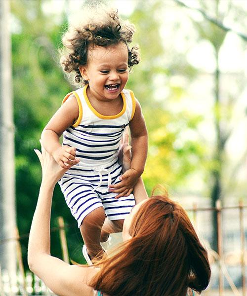 Frau lässt lachendes Kind hochleben