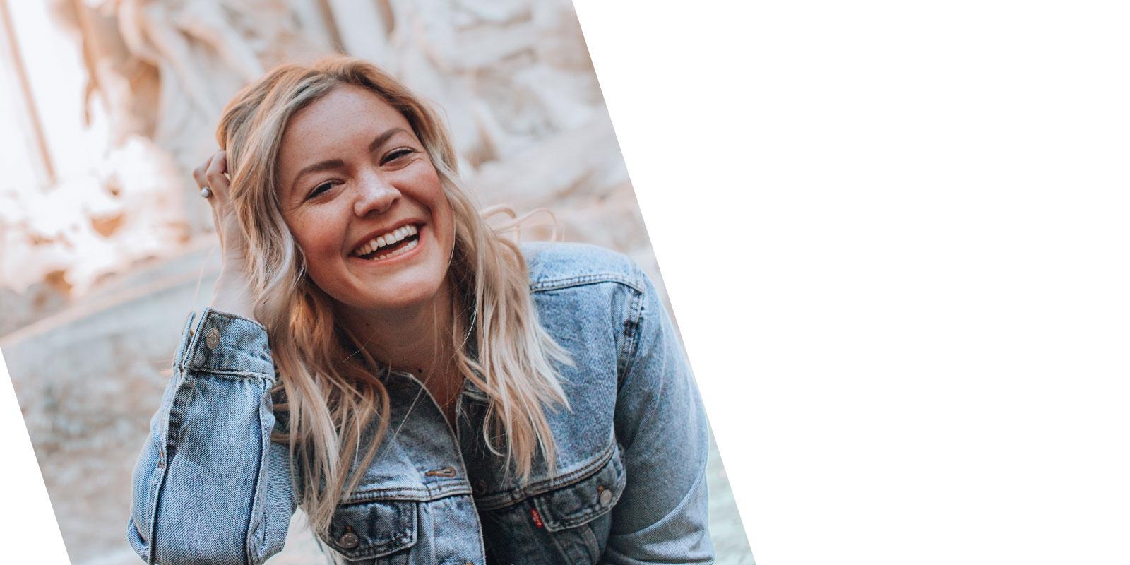 blonde Frau lachend mit Jeansjacke